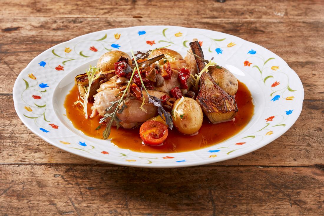 Konfitované králičí stehno s provensálskými bylinkami, olivy, malá rajčata, artyčoky a bramborové rohlíčky