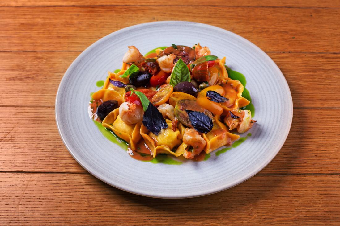 Ravioly plněné ricottou se sušenými rajčaty, krevety s malými rajčaty, česnekovým konfitem, kalamata olivami, kapary a petrželkou