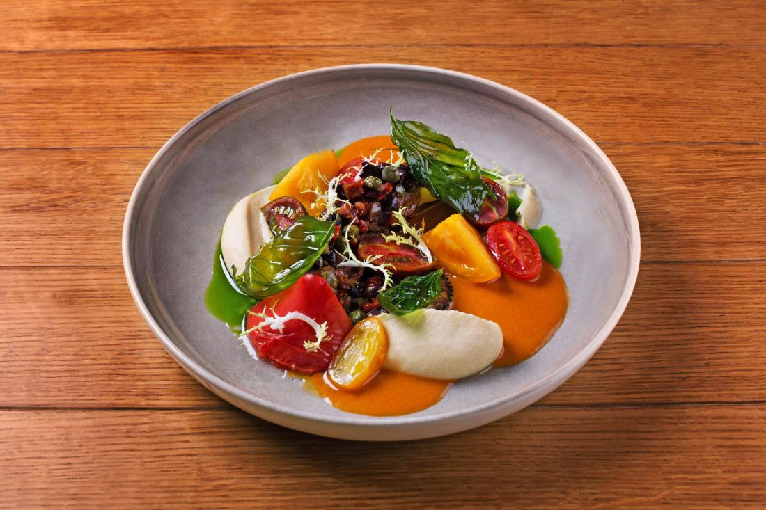 Pečená chobotnice, hummus, vinaigrette ze sušených rajčat, rajčata a omáčka z choriza