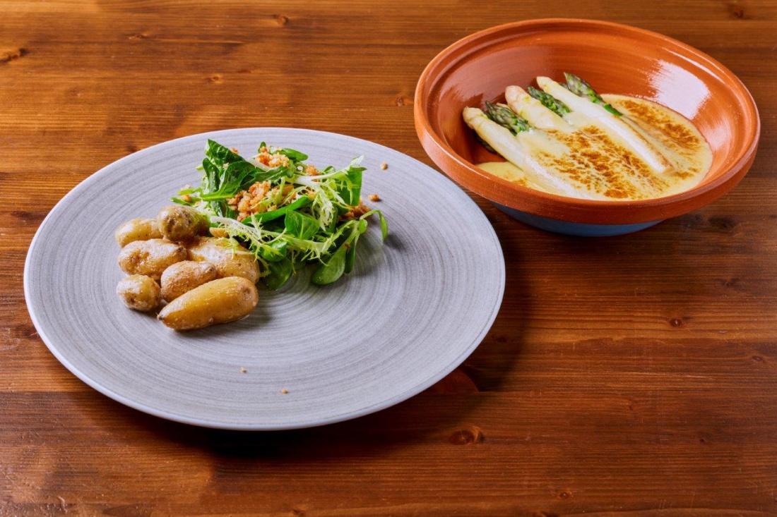 Chřest zapečený pod holandskou omáčkou, bramborové rohlíčky, rukola, mladý špenát s praženými lískovými ořechy a parmezánový crumble