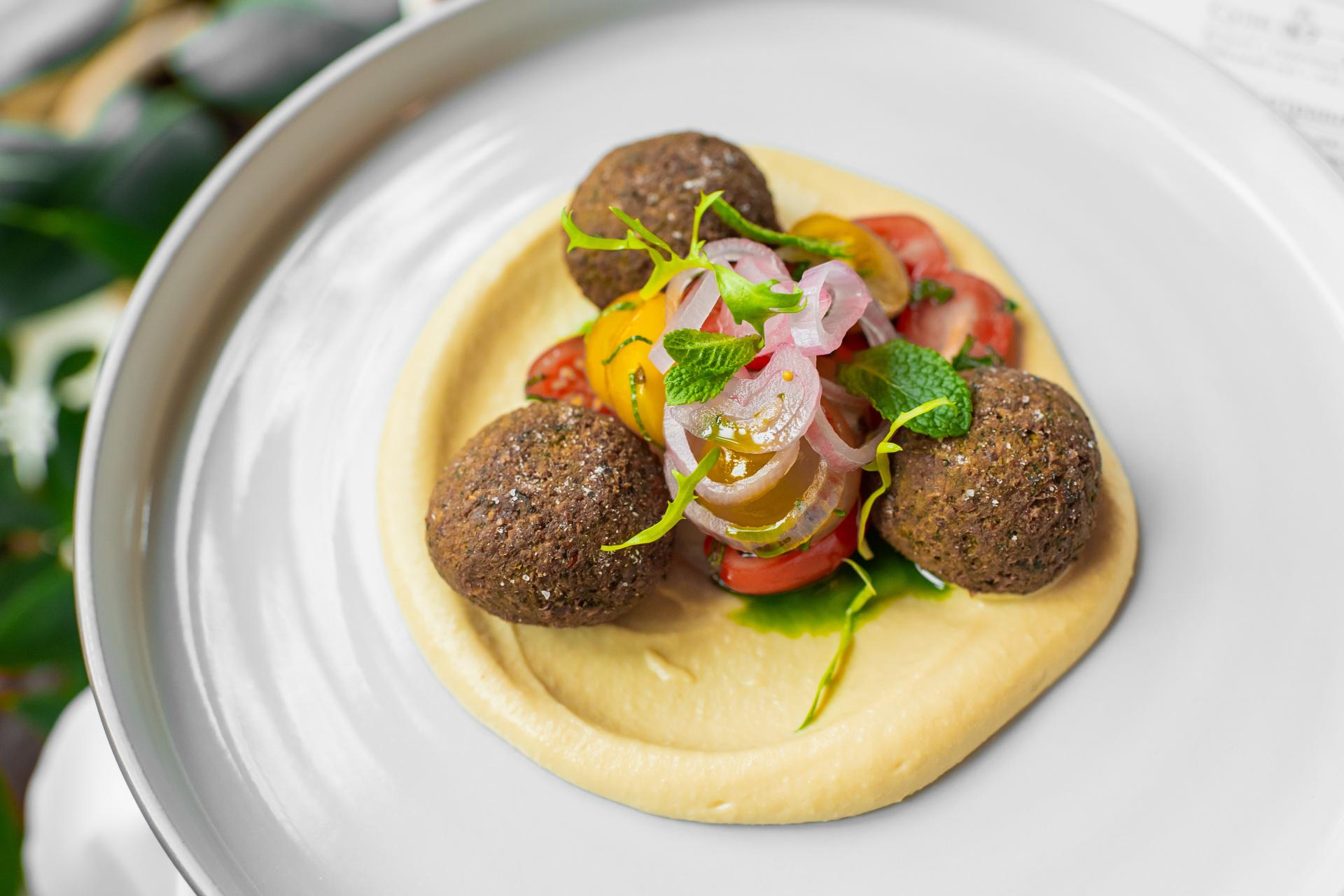 Felafel, krém z hummusu a tahini pasty, salát z malých rajčat a máty, marinovaná šalotka