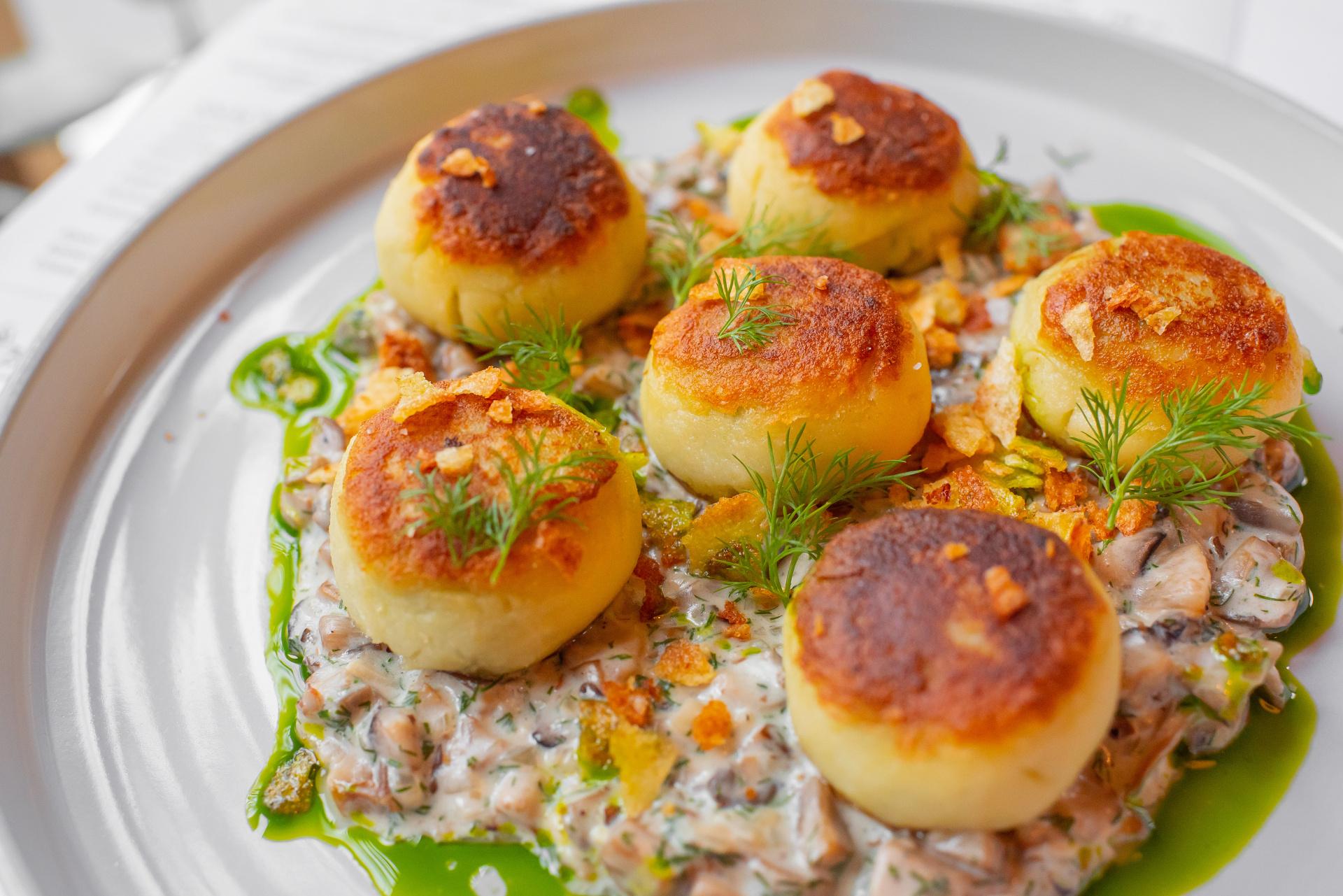 Bramborové knedlíčky plněné špenátem, houbové ragú s koprem, křupavé brambory, koprový olej